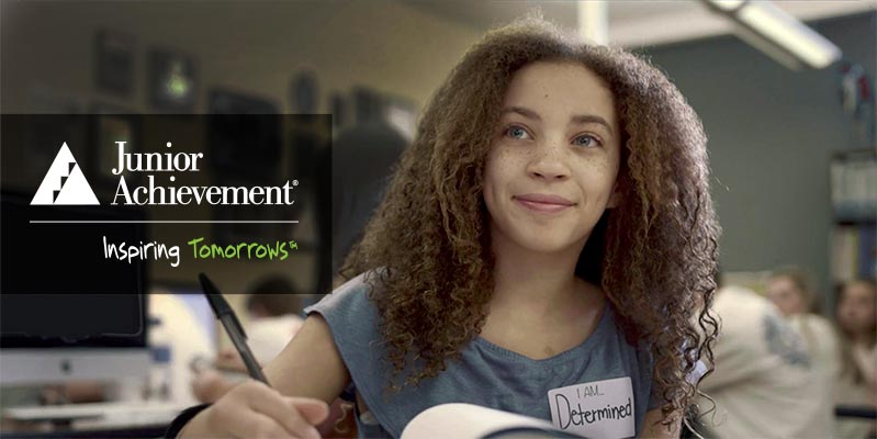 Junior Achievement Inspiring Tomorrow Logo Overlayed on Girl Smiling, wearing a nametag that says, 'I am determined'